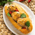 Xiu Mai in a Vietnamese baguette on a plate surrounded by chilis, coriander and tomatoes