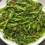 Stir Fried Water Spinach with Shrimp Paste on a plate beside a dish of shrimp sauce