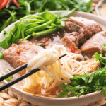 Vịt Nấu Chao in a bowl with chopsticks pulling up the noodles