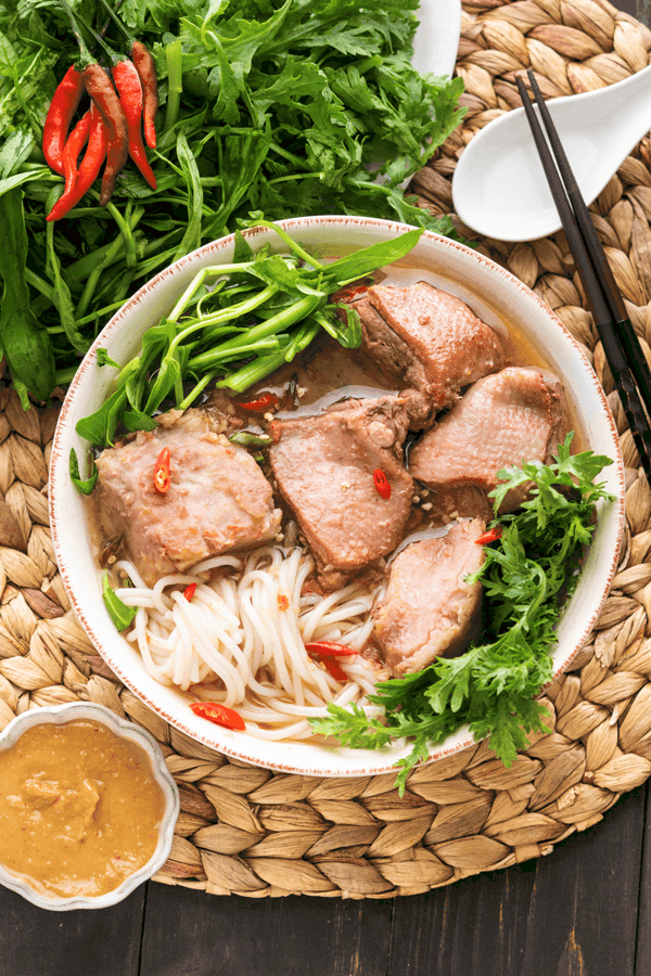 Vịt Nấu Chao in a bowl surrounded by greens, a spoon, chopsticks and dipping sauce in a dish