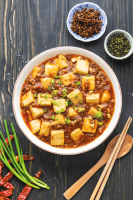 Mapo Tofu with Pork Mince in a bowl surrounded by spring onions and dried chili