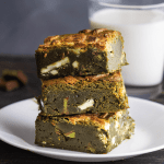 Matcha Brownies stacked on a plate in front of a glass of milk