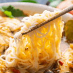 Tom Yum Noodle Soup in a bowl with chopsticks lifting noodles