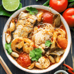 Tom Yum Noodle Soup in a bowl surounded by tomatoes, lime, chilis and chopsticks