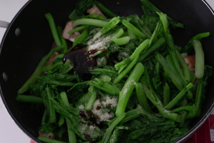 Greens and pork stir fry with oyster sauce and chicken bouillon powder on it