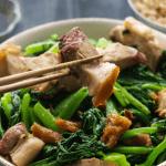 Chopsticks hoding up crispy pork belly over a bowl of stir fry