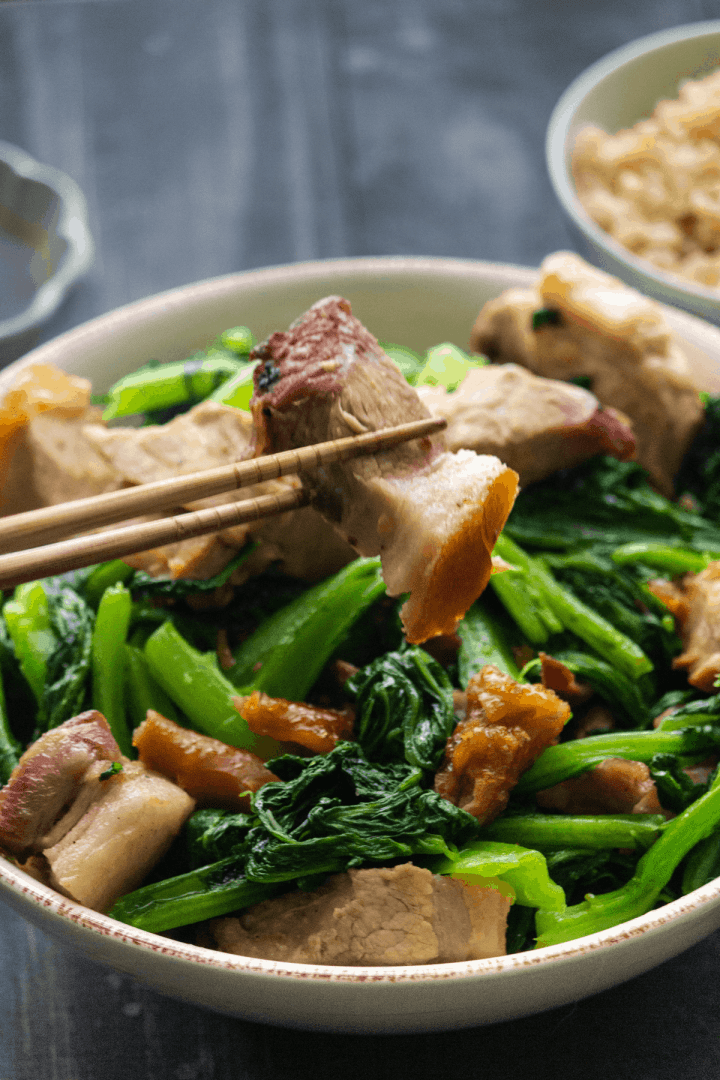 Chopsticks hoding up crispy pork belly over a bowl of stir fry.
