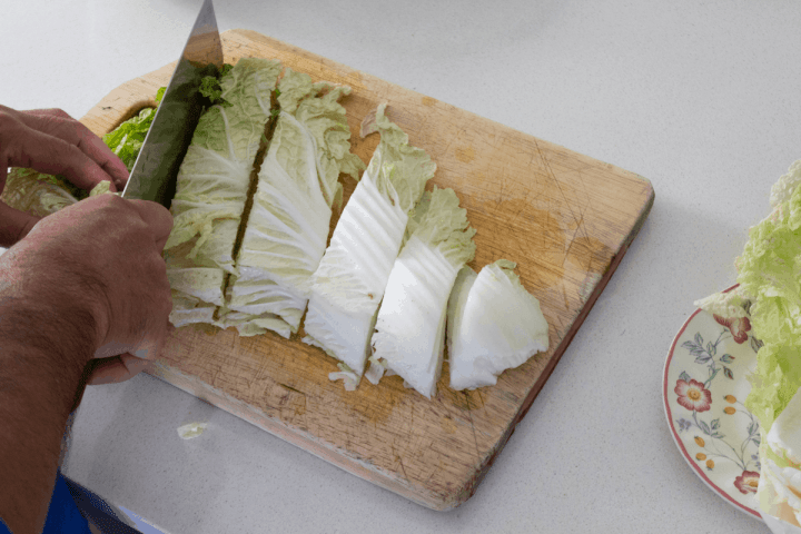 Cabbage cut into segments on a chopping board with a cleaver