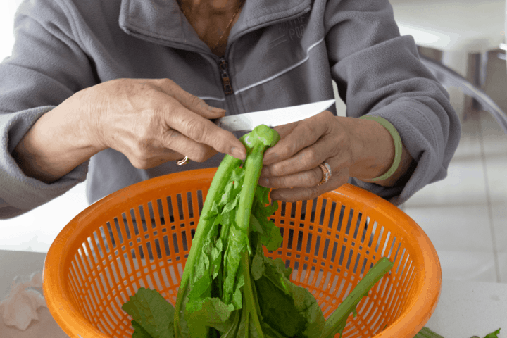 Hands using a small knife to cut the stems off jook choy over a colander