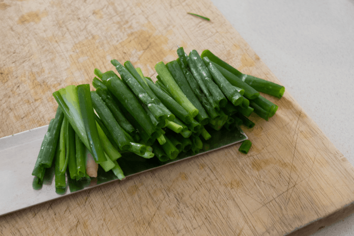 Scallion segments on a cleaver over a chopping board.