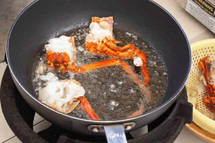 Lobster pieces in a wok with oil.