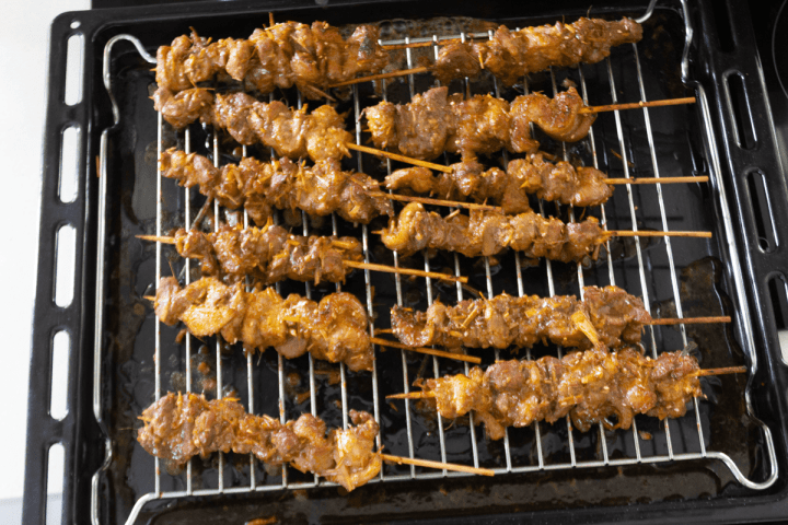 Uncooked pork skewers on an oven rack