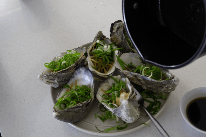 A saucepan pouring oil into oysters garnished with spring onions and ginger on a plate