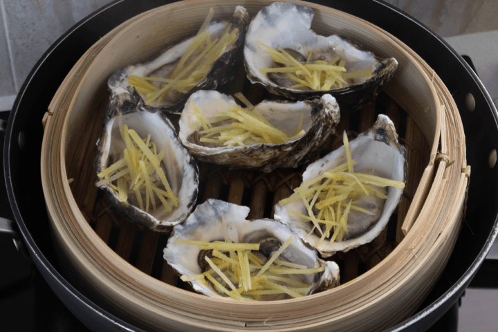 Oysters with julienned ginger on them in a bamboo steamer