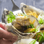 A hand holding a fork holding an oyster with ginger and shallots