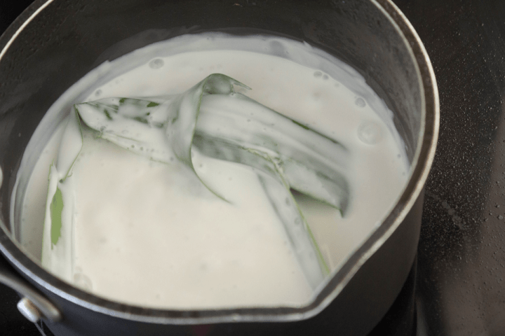 A pandan leaf tied into a knot in a pot of coconut cream.