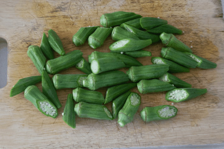 Okra halved on a chopping board.