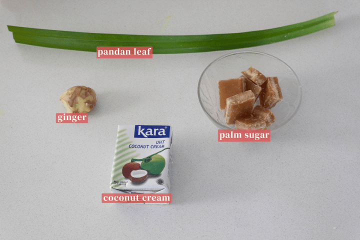 A pandan leaf surrounded by ginger, a bowl of palm sugar and a container of coconut cream.