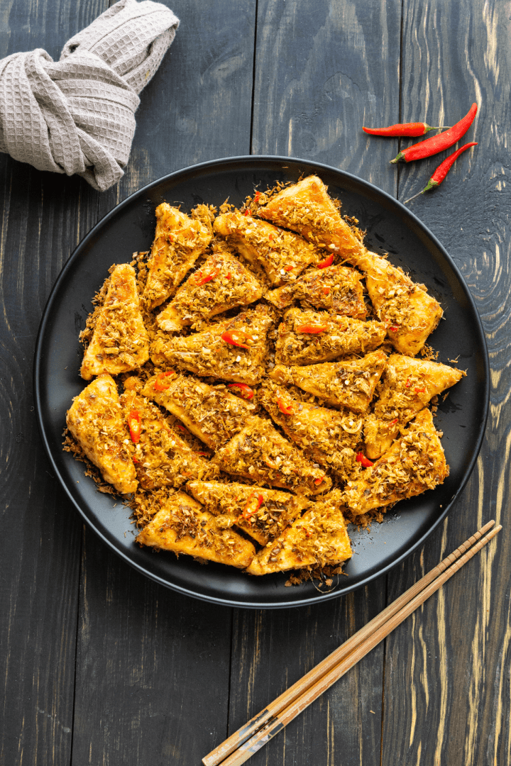 Lemongrass Chili Tofu on a plate surrounded by chili and chopsticks.