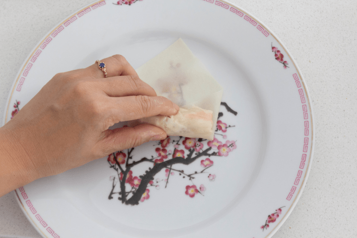 A hand rolling a spring roll up on a plate.