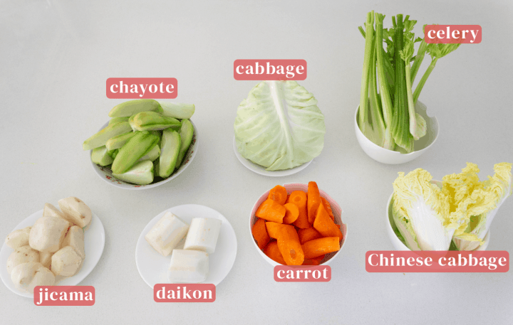 Bowls of chayote, cabbage, celery, Chinese cabbage, chopped carrots, cut daikon and jicama.