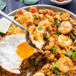 A spoonful of fried rice over a plate of Tom Yum Fried Rice.