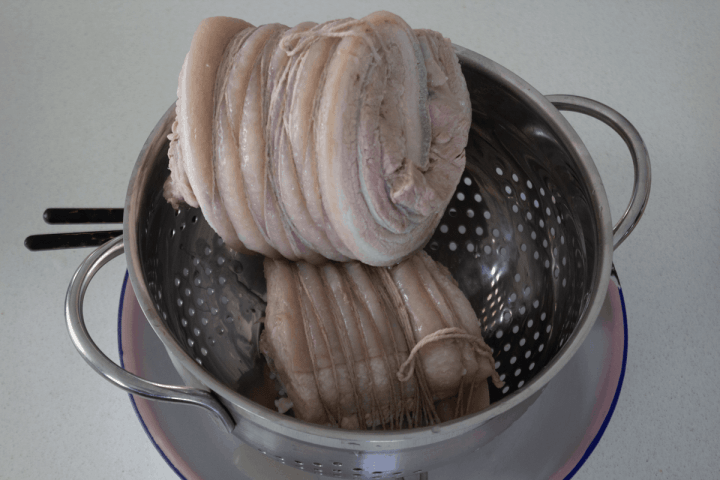 Cooked, tied and rolled pork belly.