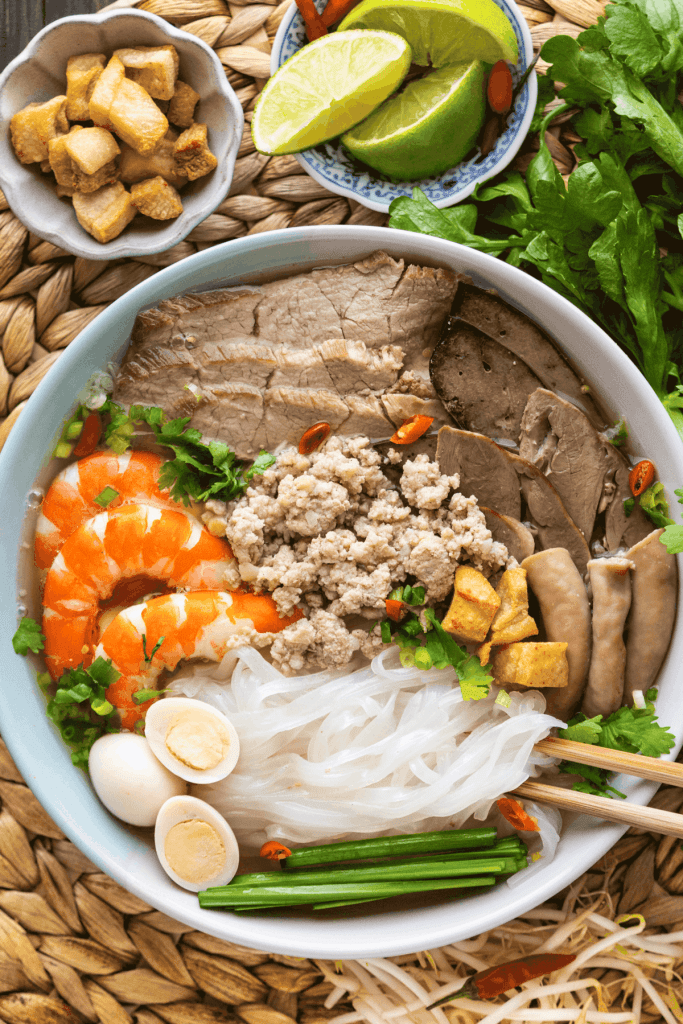 Hu Tieu Nam Vang in a bowl with chopsticks in it.
