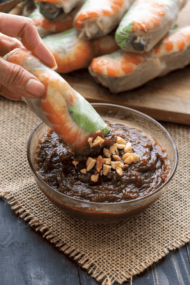 A rice paper roll dipping into Hoisin Peanut Sauce.