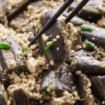 Cooked eggplant held up by chopsticks.