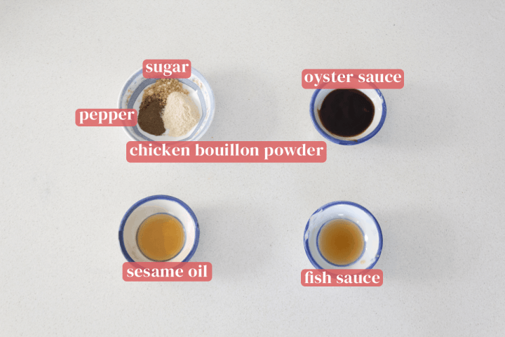 Dishes of sugar, pepper, chicken bouillon powder, oyster sauce, fish sauce and sesame oil.