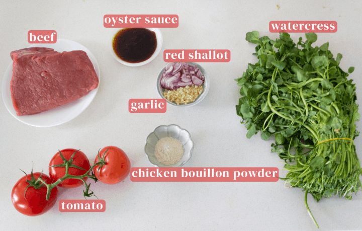 A plate of beef along with dishes of oyster sauce, chopped red shallot and garlic, chicken bouillon powder above tomatoes and a colander of watercress.