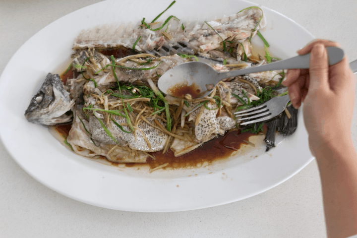 A spoon spooning sauce over fish on a plate.