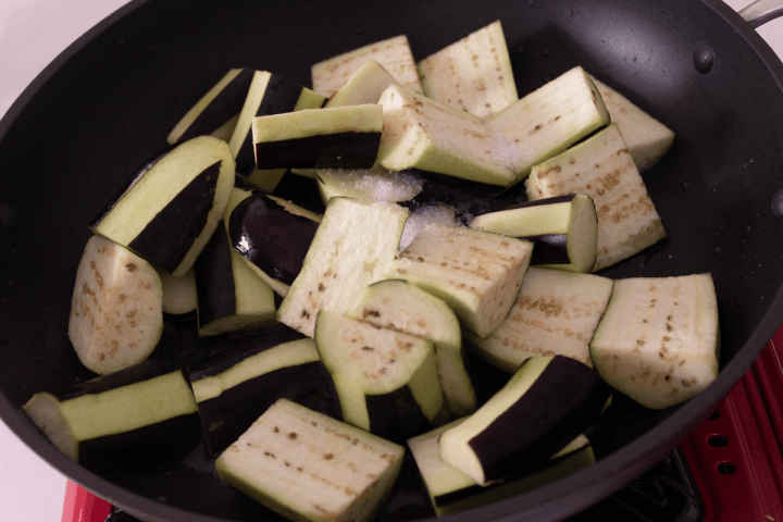 Eggplant pieces with salt in a wok.