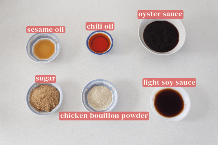 Dishes of sesame oil, chili oil, oyster sauce, sugar, chicken bouillon powder and light soy sauce.