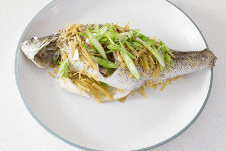 Spring onions and garlic on a fish.