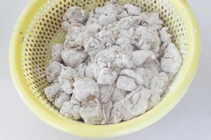 Chicken pieces coated in corn starch in a colander.