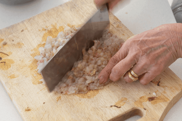 A cleaver and hand mincing prawns.
