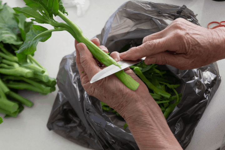 A hand holding onto a Chinese broccoli stem while a knife cuts into the skin.