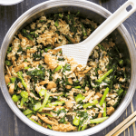 Rice Cooker Rice with Mushrooms and Chinese Broccoli with a spatula scooping into it.