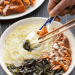 Roast Duck Noodle Soup in a bowl with a spoon and chopsticks.
