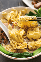 Wonton Egg Noodle Soup in a bowl with chopsticks holding noodles up.