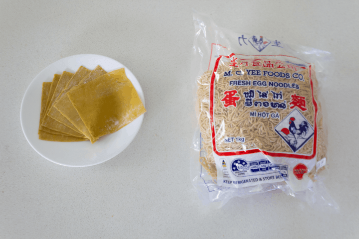 Wonton skins on a plate along with a bag of egg noodles.