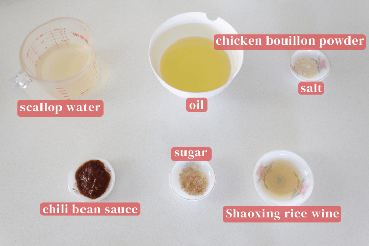 Scallop water in a measuring cup along with a bowl of oil and dishes of chicken bouillon powder, salt, sugar, Shaoxing rice wine and chili bean sauce.