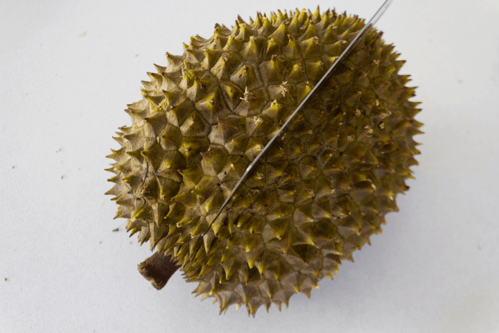 A cleaver cutting into a durian.