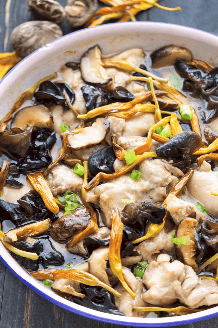 Close up of Steamed Chicken with Mushrooms and Dried Lily Flowers in a dish.