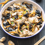 Steamed Chicken with Mushrooms and Dried Lily Flowers in a dish.
