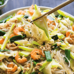 Winter Melon Stir Fry on a plate with chopsticks holding some up.