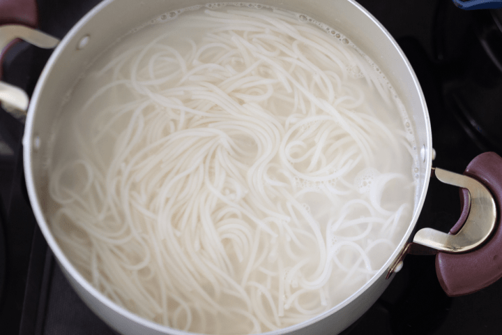 Rice noodles in a pot of water.