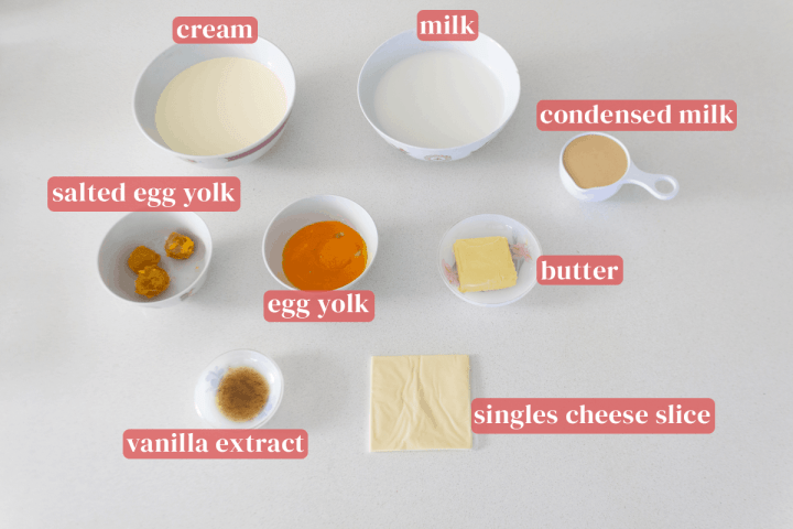 Bowls of cream, milk, egg yolks and salted egg yolks along with dishes of butter and vanilla extract next to a slide of cheese and a measuring cup of condensed milk.